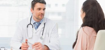 Male doctor listening to patient with concentration at desk in medical office